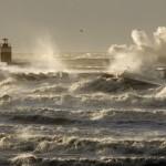 The Netherlands, IJmuiden, Storm. Waves smash against lighthouse or beacon.